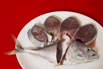 Fresh fish sliced on a white dish.