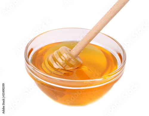 Glass bowl of honey with wooden drizzler