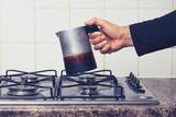 Man's hand placing espresso maker on stove