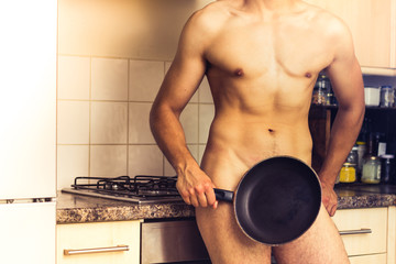 Naked chef standing by the stove with frying pan