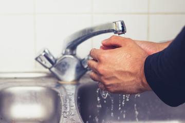 Man washing his hands in kirchen sink