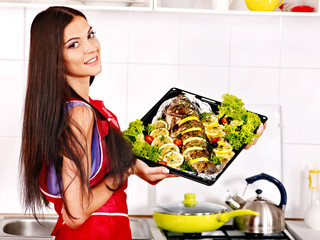 Woman prepare fish in oven.
