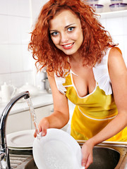 Woman washing dishes at kitchen.