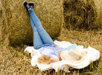 Frau schläft am Heuballen in der Nachmittagssonne