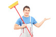 Cleaner in a uniform with a broom pointing with his arm