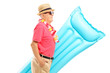 Mature man on vacation holding a swimming mattress in profile