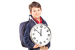 School boy with backpack holding a wall clock looking at camera