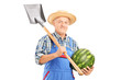 Smiling farmer holding a watermelon and a shovel