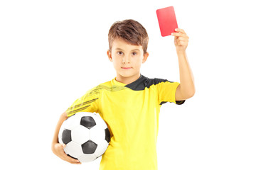 Kid in sportswear holding soccer ball and giving red card
