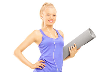 Young female holding an exercising mat