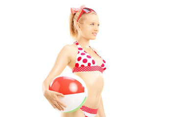 Young female in bikini holding a beach ball