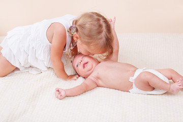 Sister kissing her baby brother