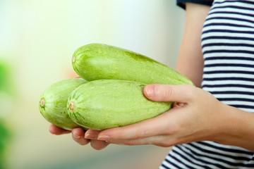 Woman hand holding raw zucchini, outdoors
