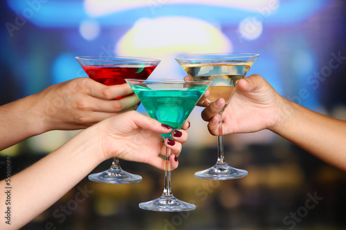 Cocktails in hands in nightclub