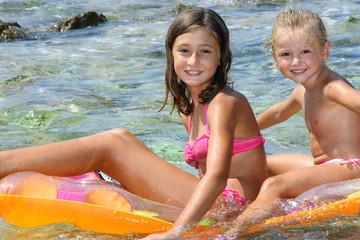Bambine al mare sul materassino
