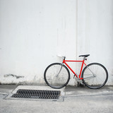 Modern red bicycle leaning on white wall