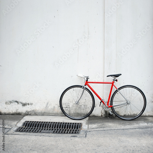 Modern red bicycle leaning on white wall - 55504994