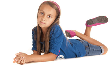 Young girl laying on the ground propped up on her elbows