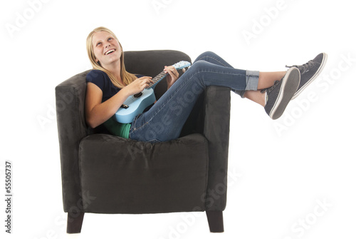 blonde teen playing a blue ukulele in a gray chair