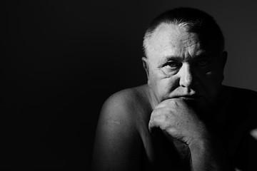 Dramatic close up portrait of depressed old man