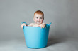 laughing baby in a blue bucket
