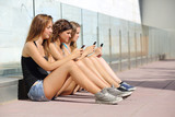 Group of three teenager girls typing on the mobile phone