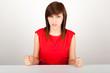 Die junge Frau sitzt wütend an einem Tisch
