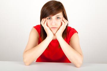 Die junge Frau sitzt müde an einem Tisch
