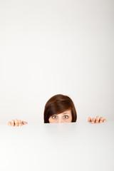 Die junge Frau versteckt sich ängstlich hinter einem Tisch