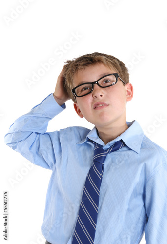 Schoolboy scratching head while thinking and looking up