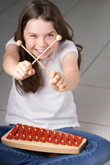 Cute dark haired girl playing Xylophone