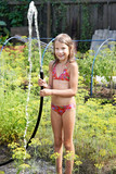 Joyful girl with garden hose and water