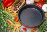 empty frying pan, vegetables and spices on wooden background