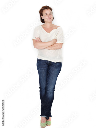 Relaxed woman leans against a white wall