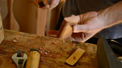 Luthier sanding a guitar piece with woodplaner