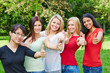 Group of women in nature holding thumbs up