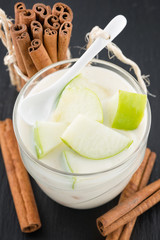 Delicious yogurt in glass with apple and cinnamon