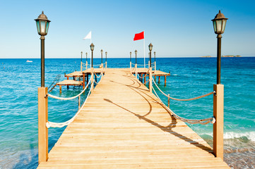 light poles and rope fence on wooden pier