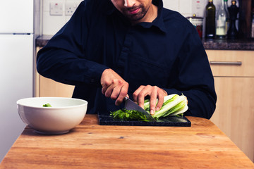 Man at kitchen table chopping lettuce