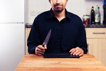 Man in kitchen with knife and chopping board