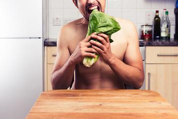 Naked man in kitchen eating lettuce