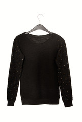 It is a black sweater with golden decor.
