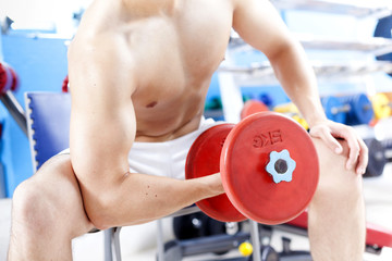 Crooped image of a man lifting weights in the gym
