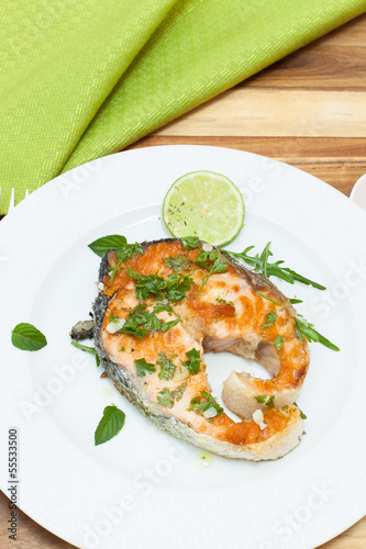 Grilled salmon steak on white plate with spices