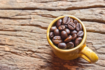 Fresh coffee beans in brown cup  on wood