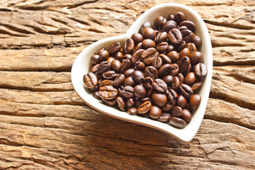 Fresh coffee beans in white heart cup  on wood