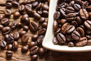 Fresh coffee beans and white cup  on wood