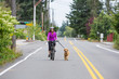 woman riding bike with a dog