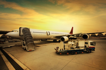The plane at the airport on loading at sunset