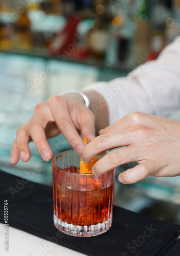 Barman is decorating drink with lemon zest